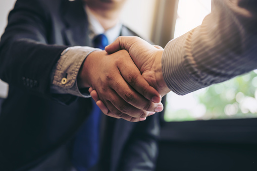 Two business men shaking hands during a meeting to sign agreement and become a business partner, enterprises, companies, confident, success dealing, contract between their firms 886031704