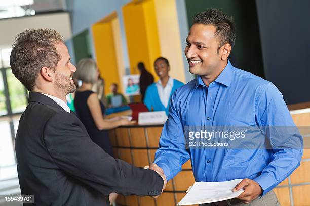 Two business men shaking hands exchanging resumes at job fair