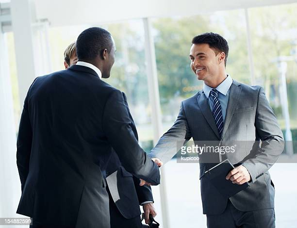 Two business men shaking hands in front of their colleague