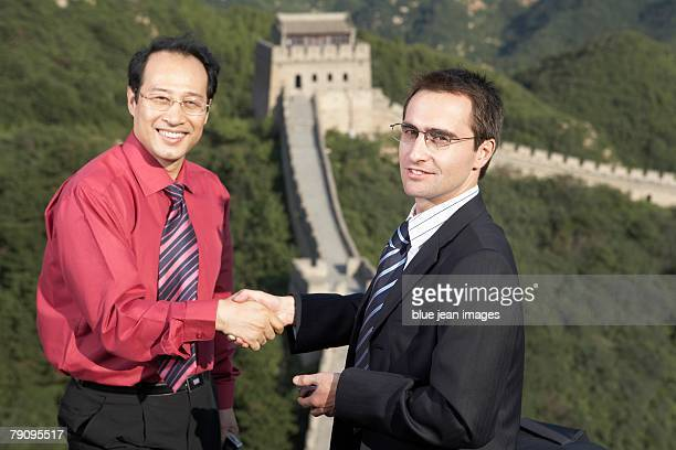 Two business men shaking hands on the Great Wall.
