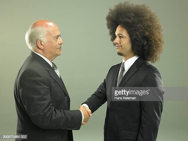 Two business men shaking hands, studio shot