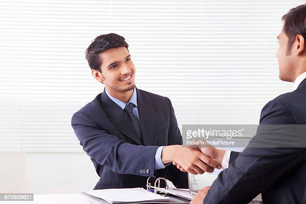 Two business men shaking hands with smile in office cabin