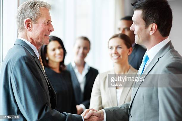 Two business men shaking hands with their teams in background