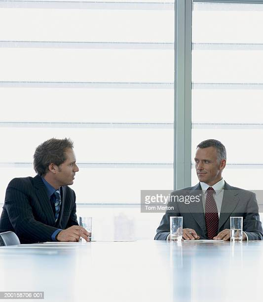 Two business men sitting at boardroom table