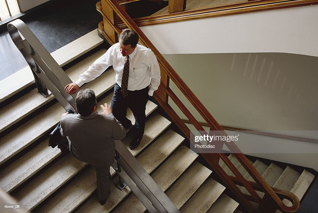 two business men stop to chat in a stairwell : Foto de stock