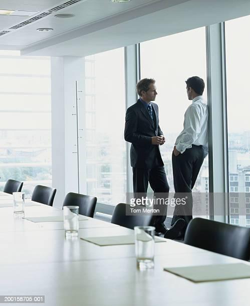 Two business men talking by window in boardroom