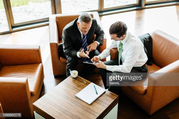 two business partners looking at digital tablet - hotel lobby stock pictures, royalty-free photos & images