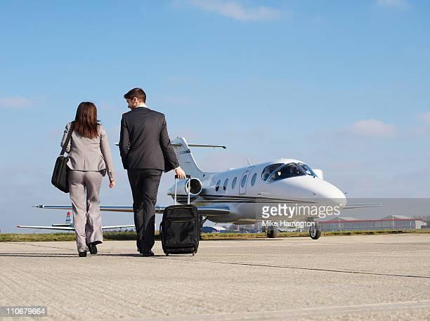 Two Business Partners Walking Towards Plane