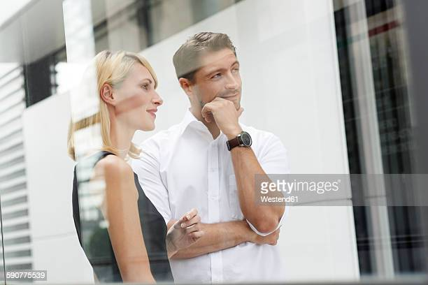 Two business partners watching something