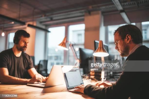 dois executivos na mesa de trabalho na noite - rivalidade - fotografias e filmes do acervo