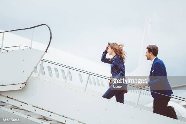 Two business people boarding airplane