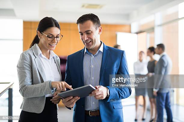 two business people discussing business strategy using digital tablet - figurantes incidentais - fotografias e filmes do acervo