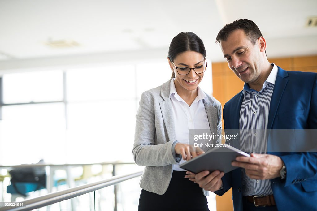 Two business people discussing business strategy using digital tablet : Stock Photo