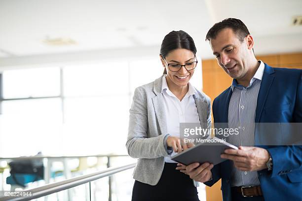 two business people discussing business strategy using digital tablet - colega fotografías e imágenes de stock