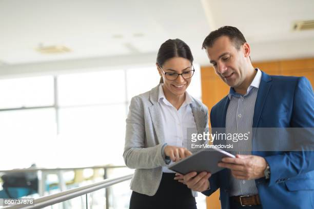 two business people discussing business strategy using digital tablet - business casual stock pictures, royalty-free photos & images