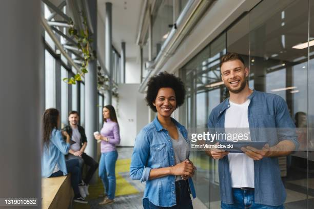 two business people discussing document in office hallway - incidental people stock pictures, royalty-free photos & images
