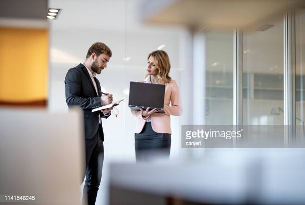 two business people discussing in the hallway - business finance and industry stock pictures, royalty-free photos & images