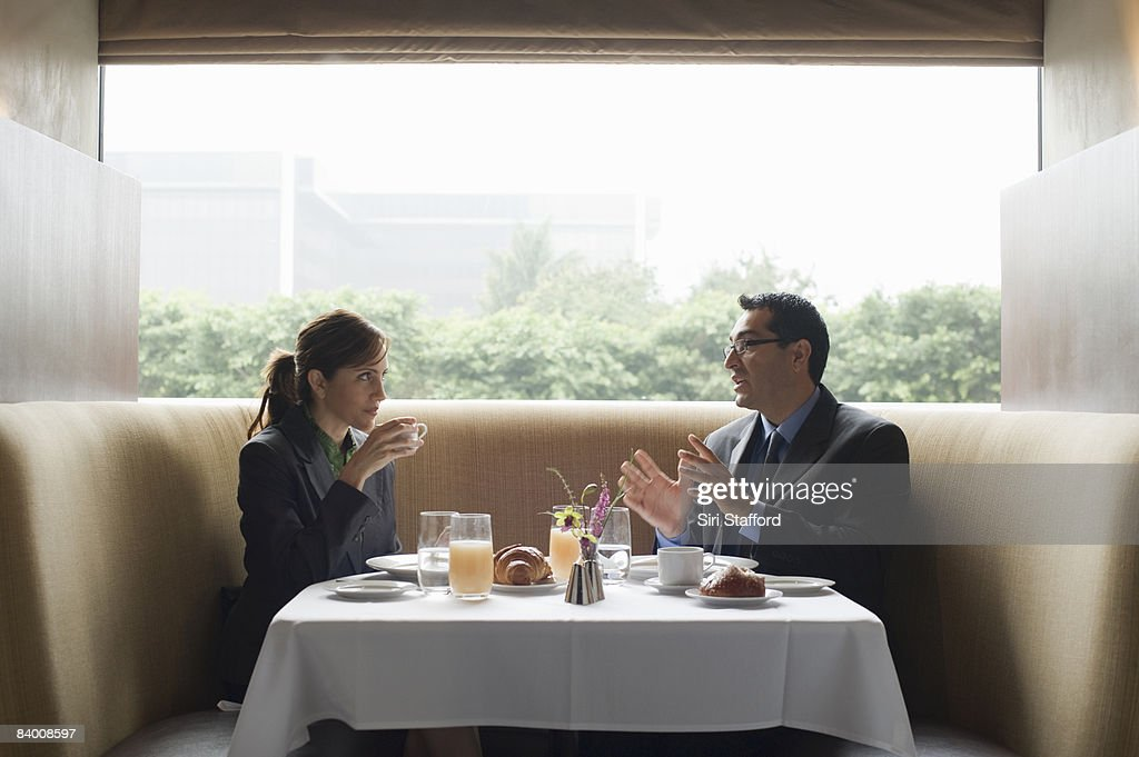 Two business people eat breakfast in restaurant. : Stock Photo