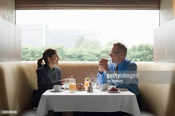 Two business people eat breakfast in restaurant.