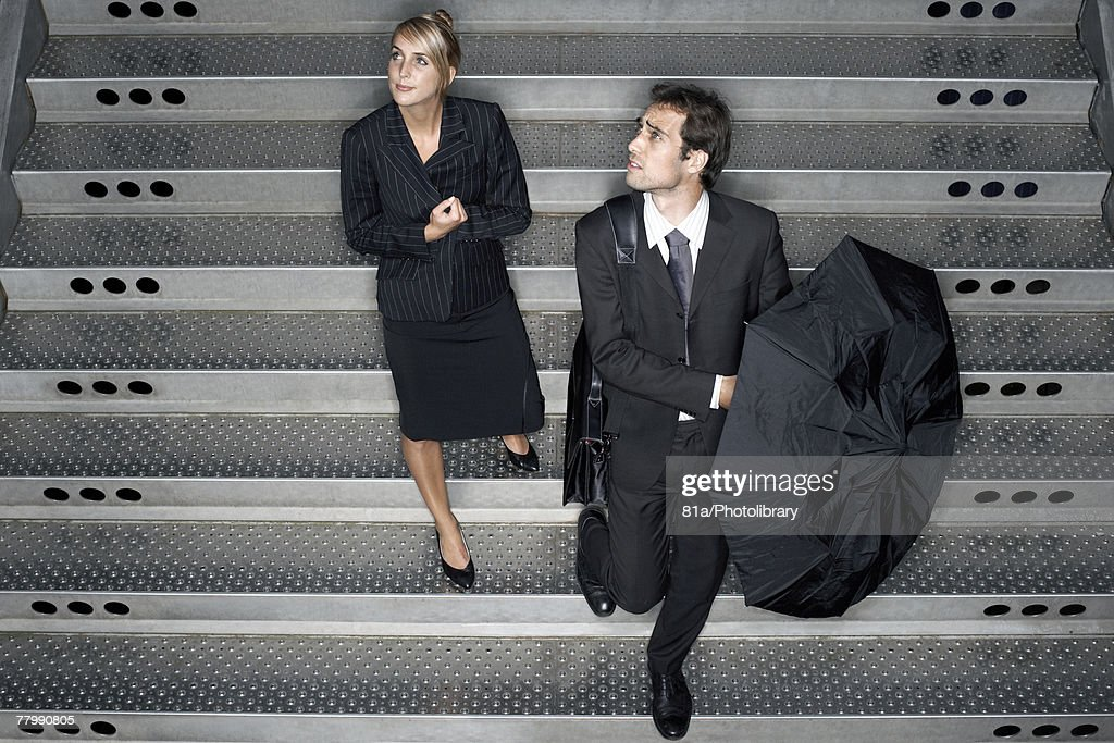 Two business people entering a train station : Stock Photo