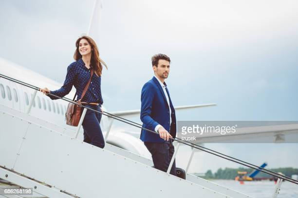 Two business people getting out of airplane
