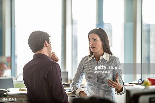 Two business people having serious discussion in modern office