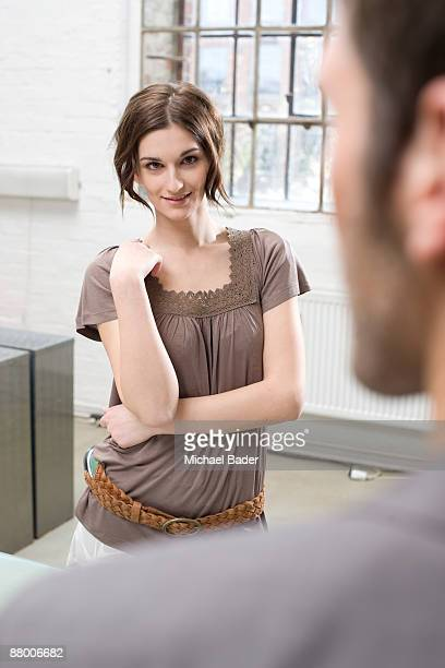 Young woman smiling at man in office, focus on woman