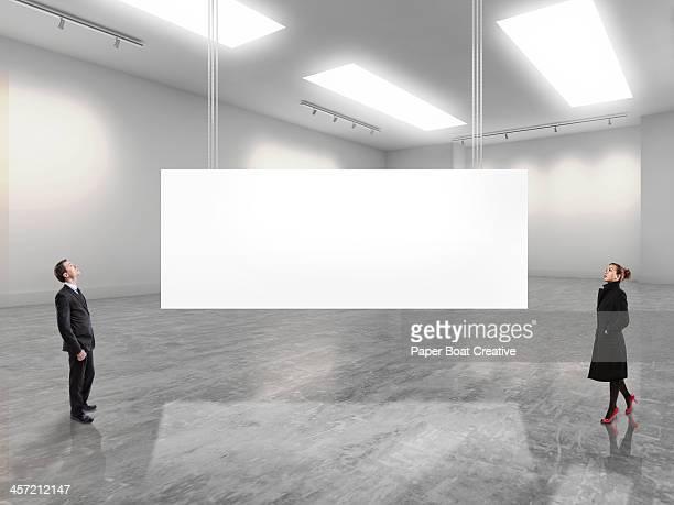 two business people looking at a large white sign - malerleinwand stock-fotos und bilder