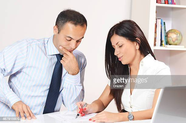 Two business people looking at financial report in modern office