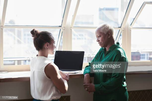 two business people looking at laptop by window - manager stock pictures, royalty-free photos & images