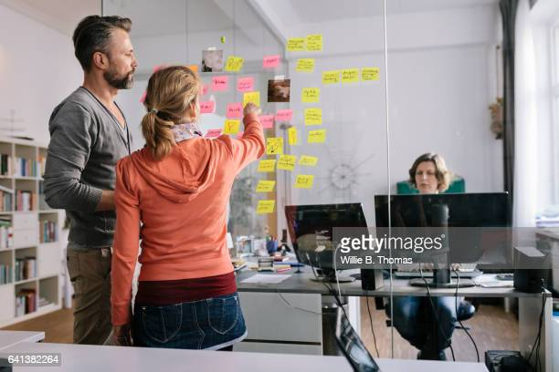 Two business people looking at post-it notes
