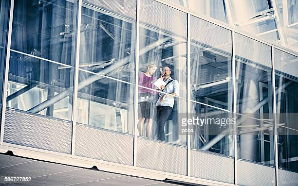 Two Business people  Looking Out of an Office Building