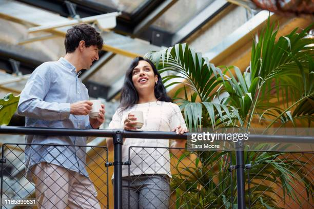 two business people looking out on balcony with coffee cup - office stock pictures, royalty-free photos & images