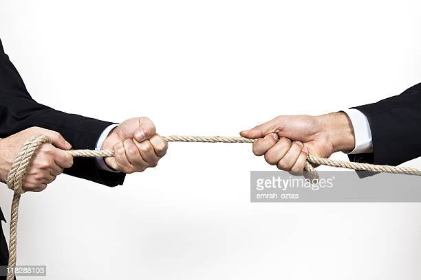 Two business people pulling rope in tug of war on white