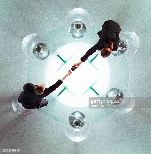 Two business people reaching across glass table, overhead view