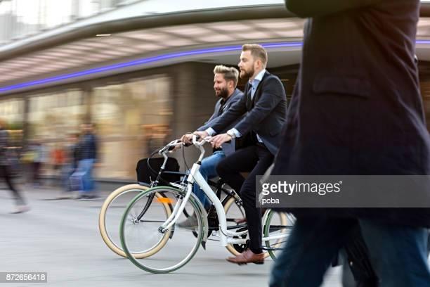 Två affärsmän ridning cykel på staden gatan