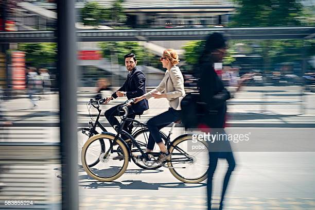 two business people riding bicycle - responsible business stock photos and pictures