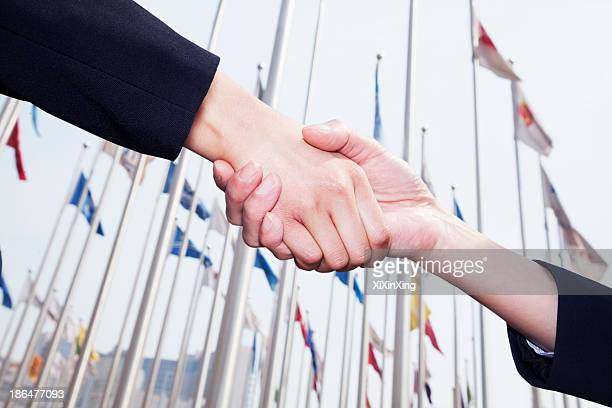 Two business people shaking hands in Beijing, flags flying in the background
