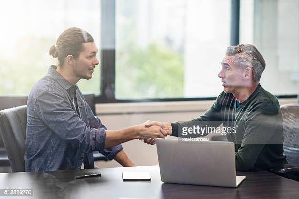 Two business people shaking hands on an interview.