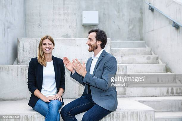 Two business people sitting on concrete steps
