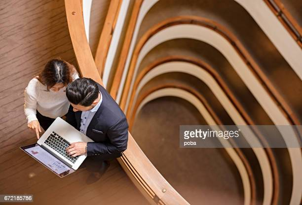 Two Business People Standing in the office building  and Using Laptop