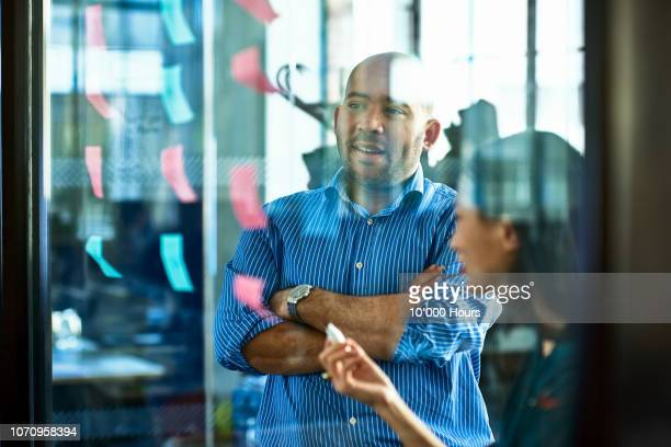 two business people strategising and using sticky notes - thinking outside the box englische redewendung stock-fotos und bilder