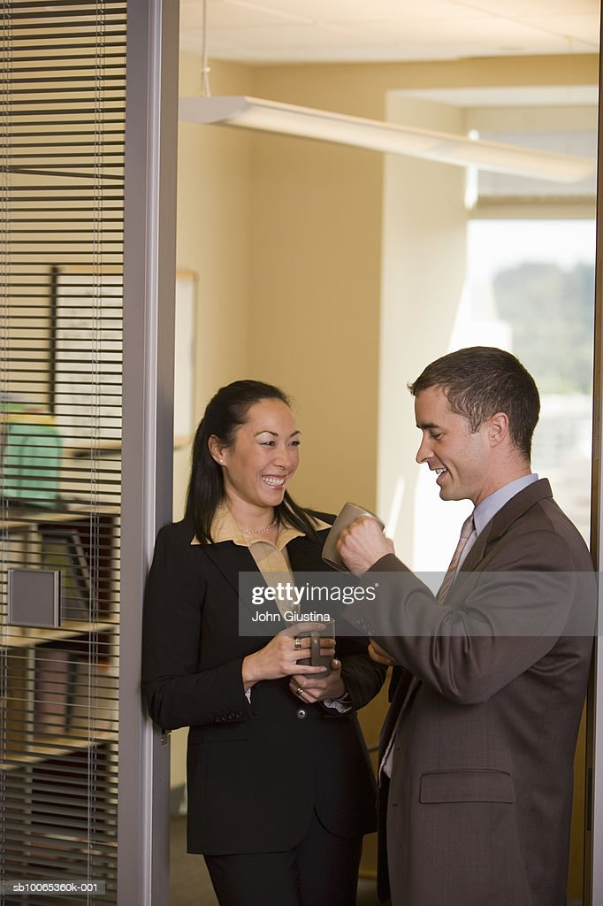 Two business people talking in hallway, smiling : Foto stock