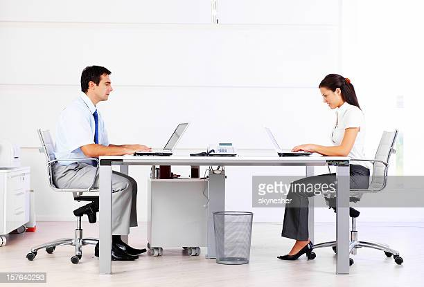 Two business people typing on laptop in the office.