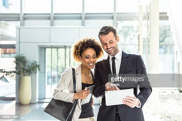 Two business people using a digital tablet in an office