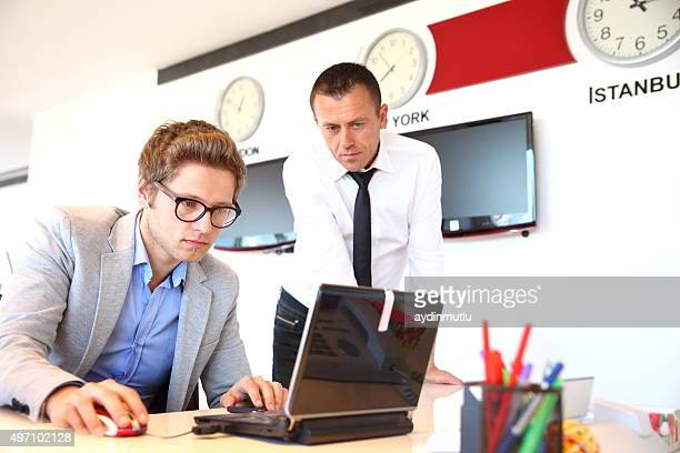 Two business people using a laptop