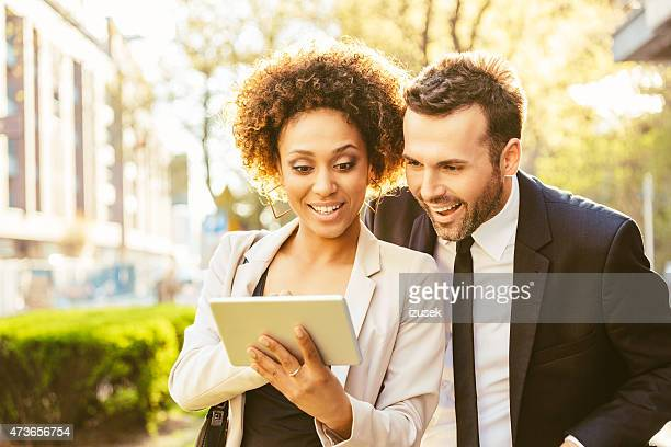 Two business people using digital tablet outdoor at sunset
