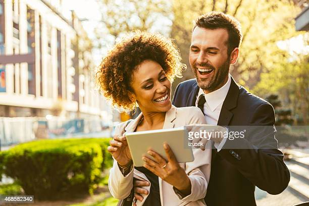 Two business people using digital tablet together outdoor