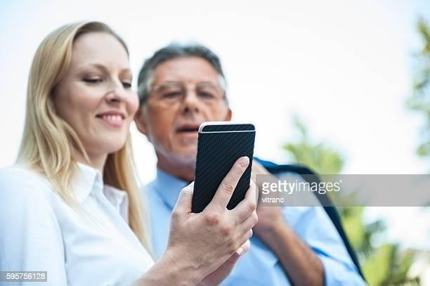 Dos personas de negocios utilizando teléfonos inteligentes al aire libre