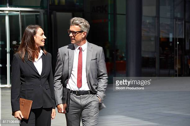 two business people walking along together - gemeinsam gehen stock-fotos und bilder